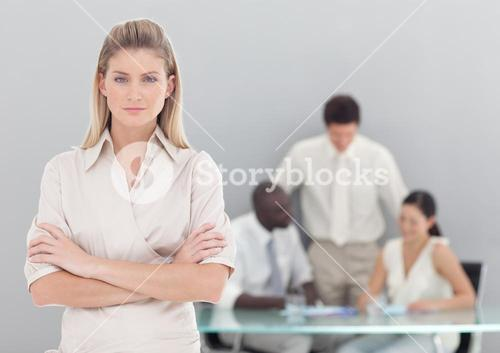 Portrait of a serious businesswoman standing with her collegues