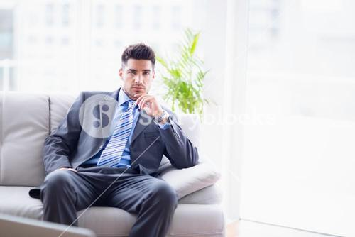 Serious businessman sitting on the sofa looking at camera