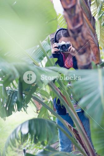 Young brunette taking a picture in a forest