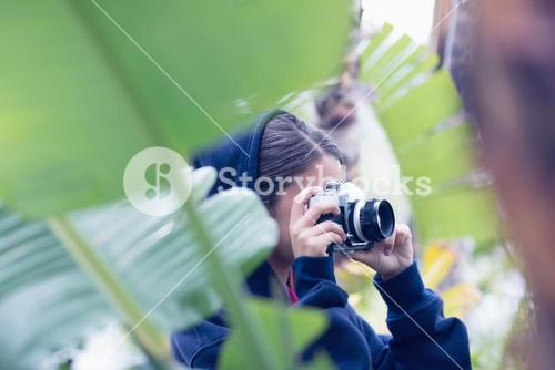Young woman taking a picture in a forest