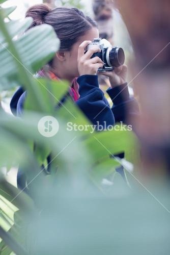 Young woman taking a picture in a wooded area