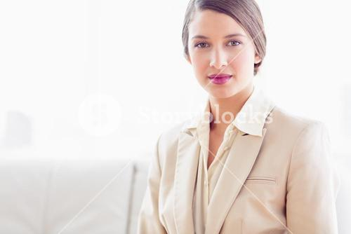 Young businesswoman sitting on sofa looking at camera