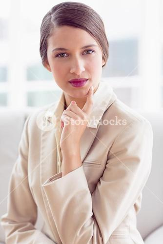 Thinking businesswoman sitting on sofa looking at camera