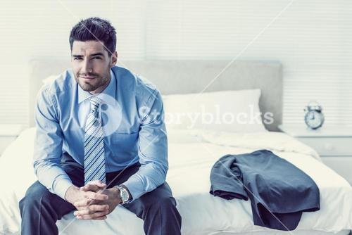 Handsome businessman sitting on bed looking at camera