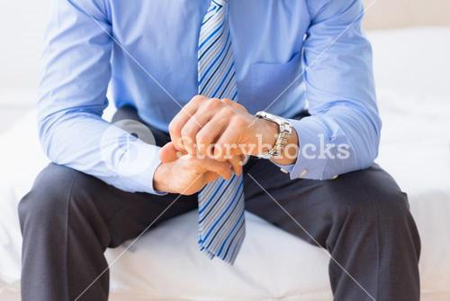 Businessman sitting on bed checking the time