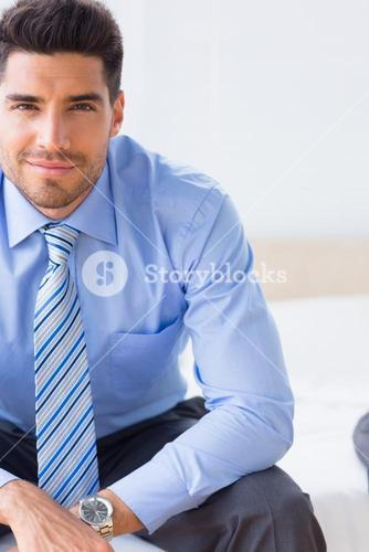 Businessman sitting on bed smiling at camera