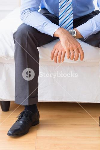 Businessman sitting on his bed