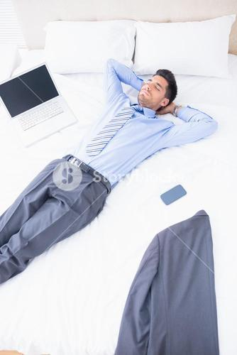 Napping businessman lying on his bed