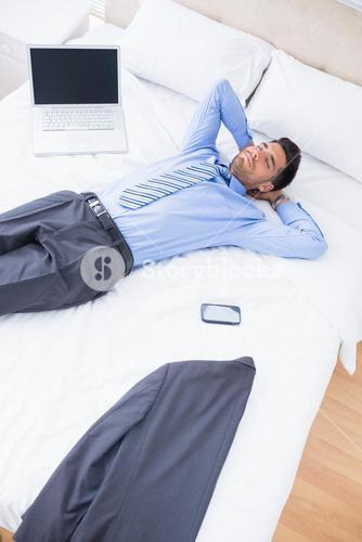 Sleeping handsome businessman lying on his bed