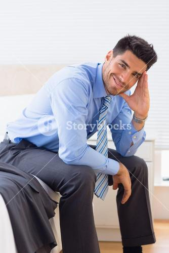 Happy businessman sitting at edge of bed looking at camera