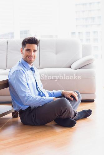 Handsome businessman sitting on the floor