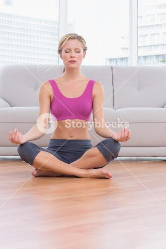 Fit blonde meditating in lotus pose