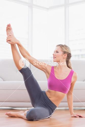 Athletic blonde sitting on floor stretching leg up