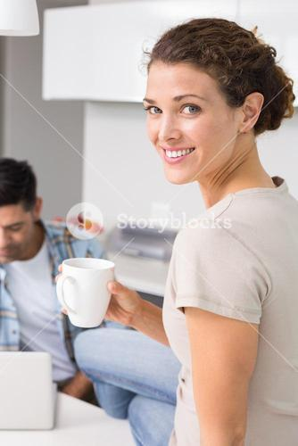 Cheerful woman drinking coffee while partners uses laptop