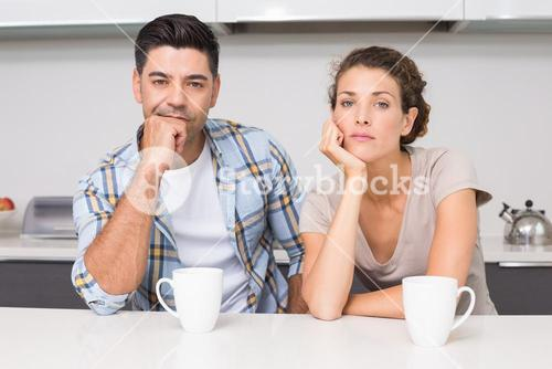 Fed up couple having coffee looking at camera
