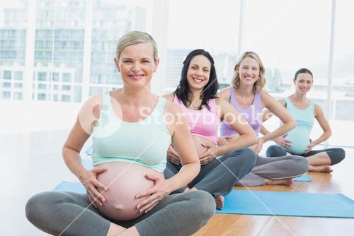 Pregnant women in yoga class sitting on mats touching their bumps