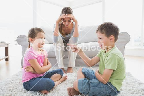 Fed up mother listening to her young children argue