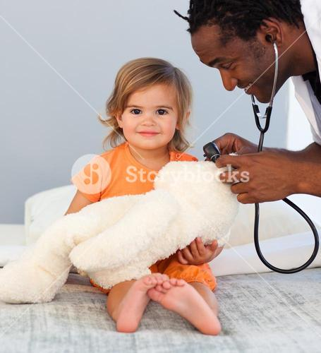 Childrens doctor exams a little girl with stethoscope