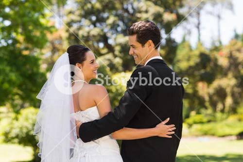 Newlywed couple with arms around in park