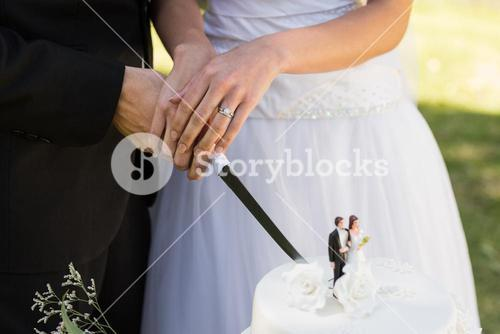 Mid section of a newlywed cutting wedding cake