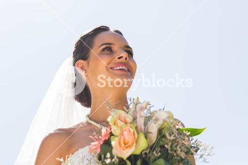 Smiling beautiful bride with bouquet against clear sky