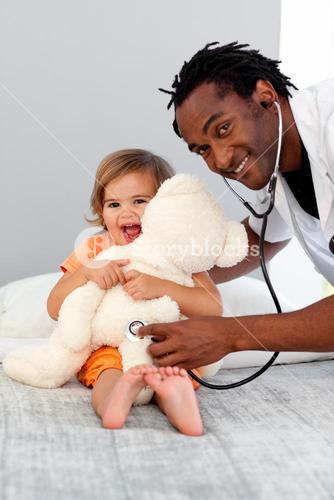 Happy doctor examining a little girl at hospital