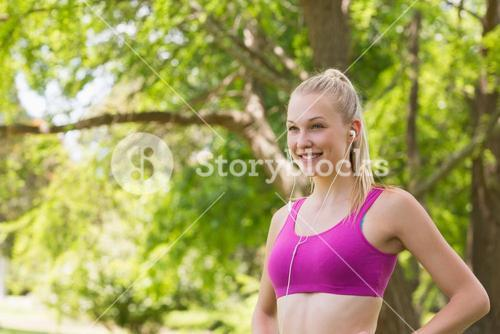 Healthy woman in sports bra jogging in park
