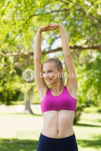 Beautiful woman in sports bra stretching hands up in park