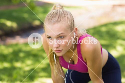 Tired beautiful woman in sports bra at park