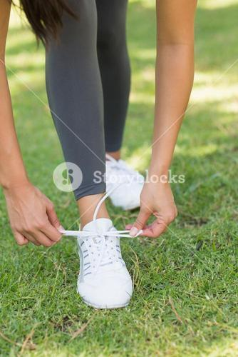 Low section of woman tying shoe lace at park