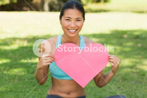 Cheerful woman holding heart shape board in park