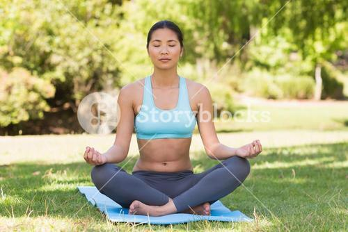 Sporty woman in lotus pose with eyes closed at park