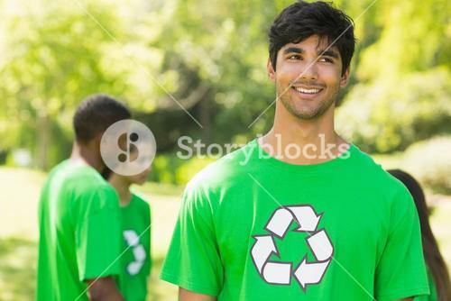 Smiling man wearing green recycling t-shirt in park