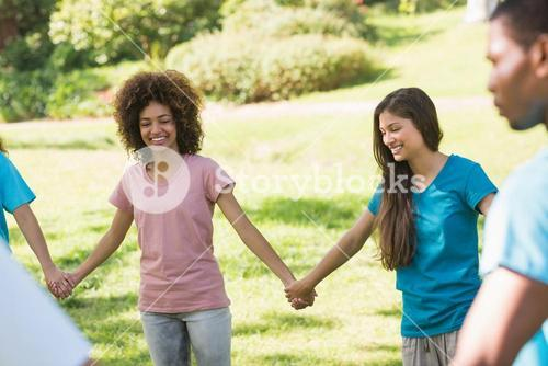 Friends holding hands in circle at park