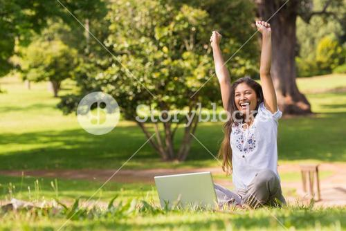 Cheerful woman raising hands with laptop in park