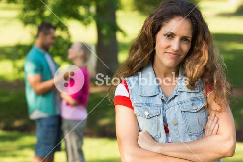 Angry woman with man and girlfriend in background at park