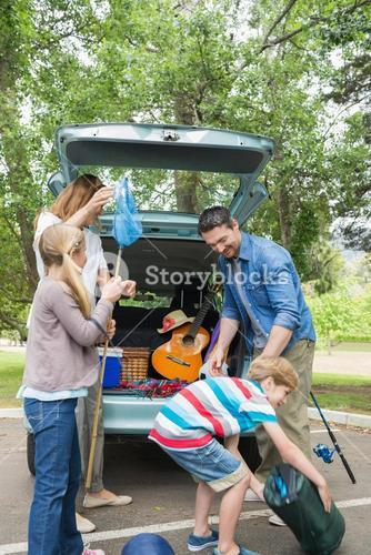 Family unloading car trunk while on picnic