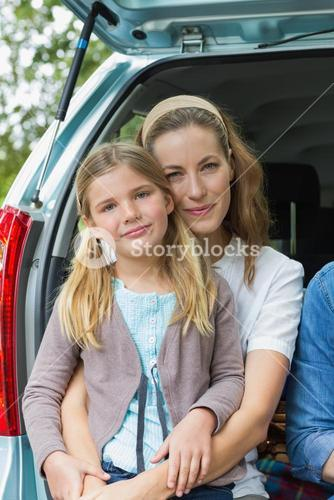 Smiling mother and daughter sitting in car trunk