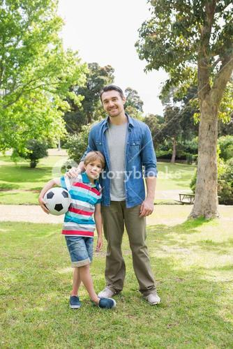 Smiling father and son with ball at park