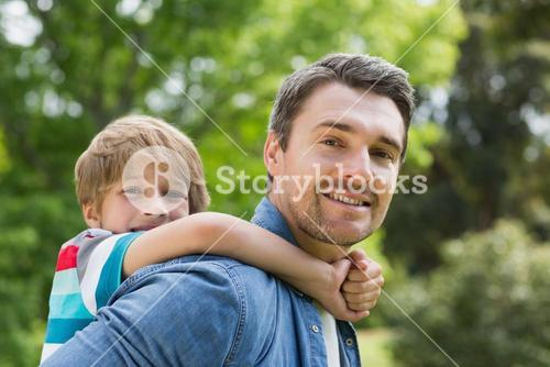 Father carrying young boy on back at park