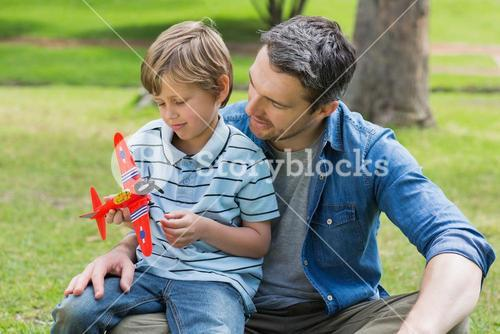 Boy with toy aeroplane sitting on fathers lap