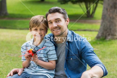 Boy with toy aeroplane sitting on fathers lap at park