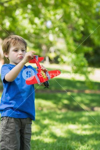 Cute boy with toy aeroplane at park
