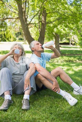 Mature couple drinking water at park