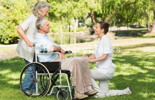 Women with mature man sitting in wheel chair at park