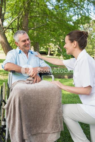 Woman with father sitting in wheel chair at park