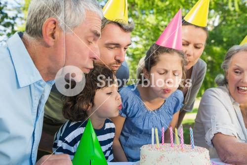 Extended family in party hats blowing birthday cake