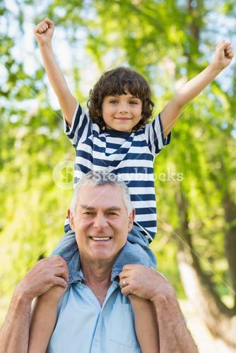 Grandfather carrying son on shoulders at park