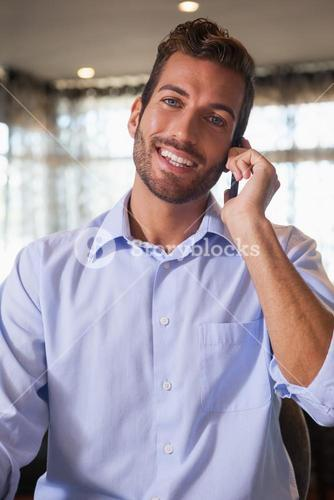 Happy businessman talking on the phone after work