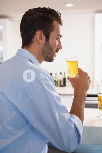 Handsome businessman drinking glass of beer after work